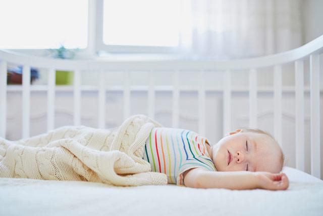 Dziewczynka-noworodek otulona kocykiem iśpiąca nawznak wbiałym łóżeczku.