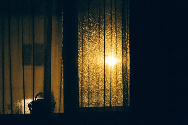 Noc iokno, przezktóre zzewnątrz wpada sztuczne światło.
