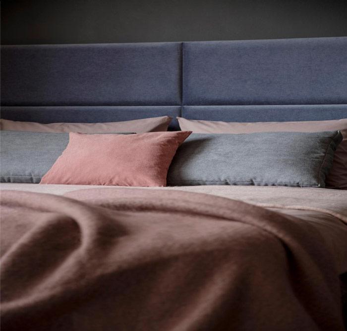 Nowoczesne tapicerowane łóżko wkolorze stalowym zpościelą inarzutą wstonowanych łososiowych odcieniach