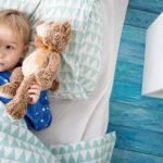 Cierpiący na dziecięcą bezsenność mały chłopiec, który leży w swoim łóżku z przytulanką i mimo zmęczenia nie może zasnąć.]