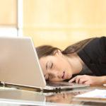 """""""Uzależniona od snu"""" kobieta śpiąca przy stole – na swoim laptopie - zdrowy-sen.eu"""