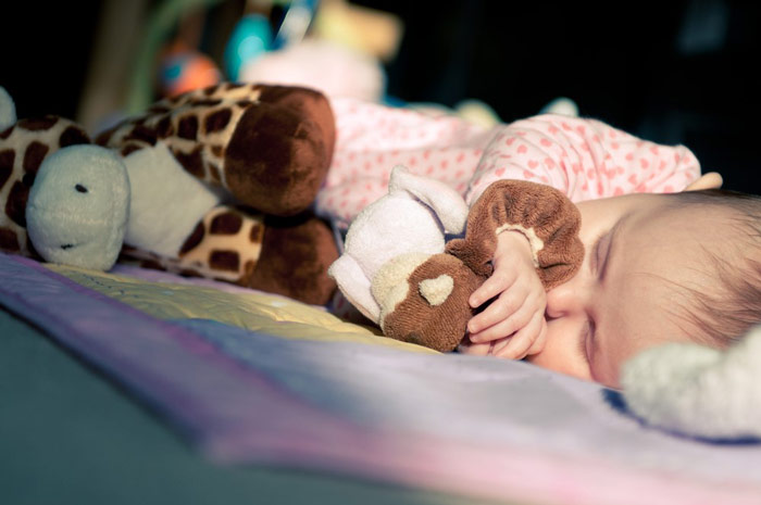 Małe dziecko śpiące przyświetle wswoim pokoju zpluszową przytulanką - zdrowy-sen.eu