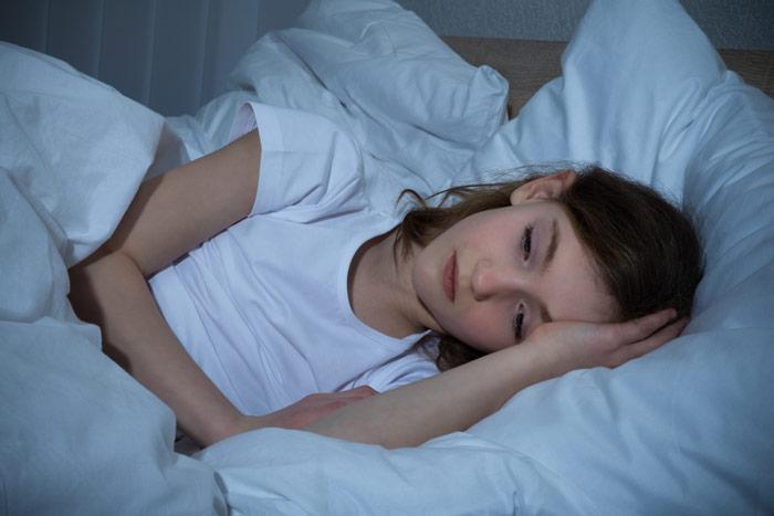 Mająca problemy ze snem nastolatka leżąca wswoim łóżku.