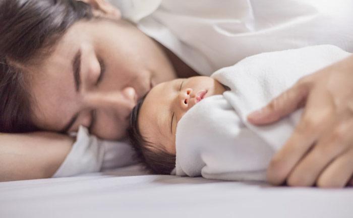 Śpiący spokojnym snem niemowlak dość ciasno otulony kocykiem - zdrowy-sen.eu