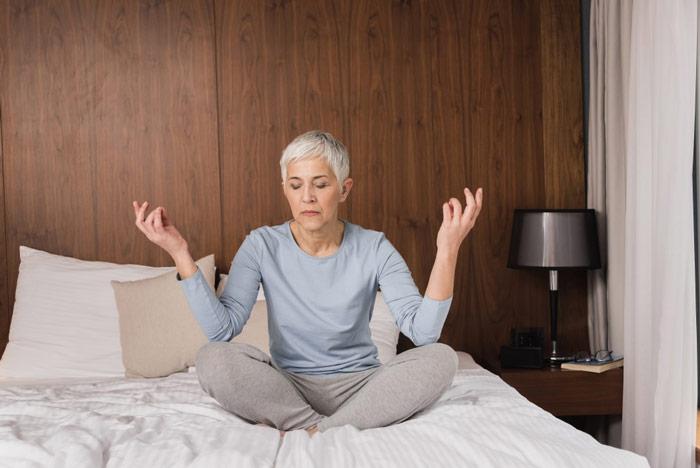 Medytująca przed snem kobieta, która siedzi poturecku nałóżku wsypialni - zdrowy-sen.eu