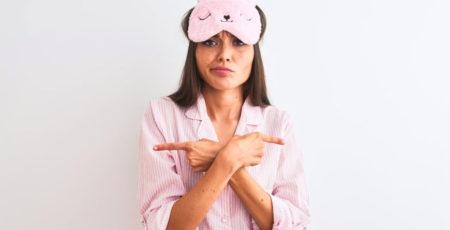 Kobieta w różowej piżamie zastanawiająca się nad prawidłowym kierunkiem spania - zdrowy-sen.eu