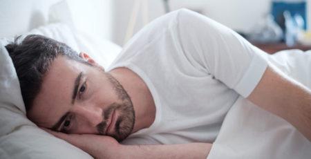 Cierpiący na ciągłe zmęczenie mężczyzna w pościeli - zdrowy-sen.eu