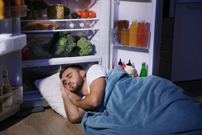 Mężczyzna śpiący napodłodze wupalną noc przyotwartej lodówce - zdrowy-sen.eu