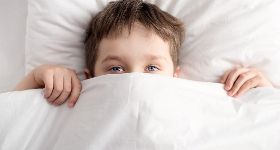 Kilkuletni chłopiec w pościeli przykryty do połowy twarzy, walczący z bezsennością - zdrowy-sen.eu